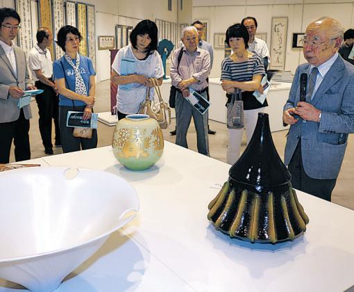 作品を解説する吉田さん(右)=小松市のサイエンスヒルズこまつ