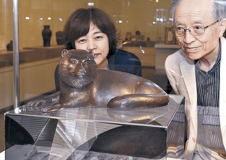 タヌキをかたどった置物に見入る関係者=加賀市美術館
