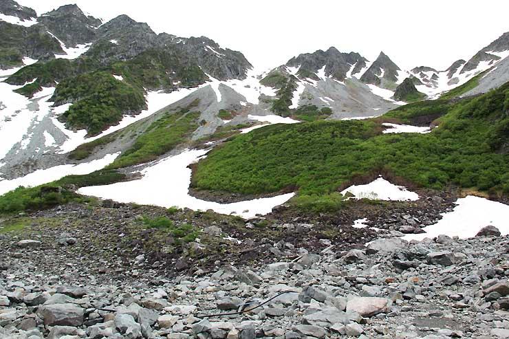 例年なら一帯を覆っている雪が見られず、岩場がむき出しになっている涸沢のテント場(手前側)=6月29日