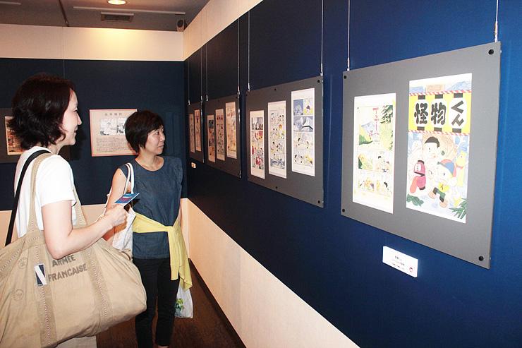 新たに展示に加わった複製原画を見る来館者