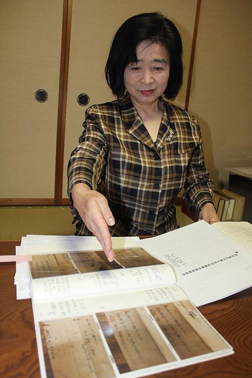経典の写真について説明する五十嵐さん=富山市愛宕町の自宅