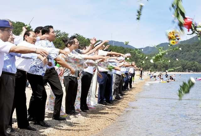 参加者が海へ花を投げ入れ、海難事故防止とにぎわいを祈願した海開き式=10日、福井県敦賀市の気比の松原海水浴場