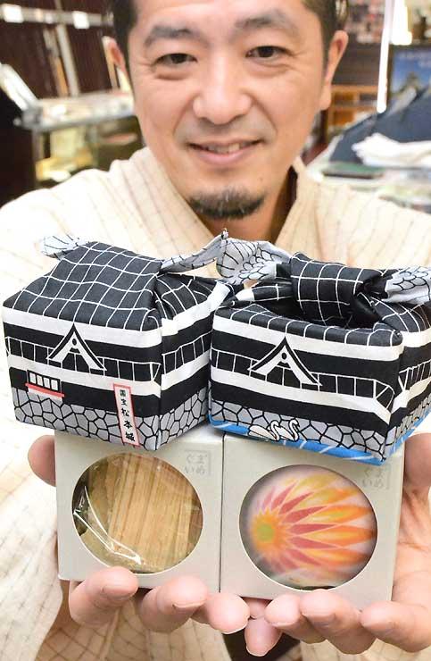 菓子が入った小箱(下)を手拭いで包み、松本城の姿を模した新商品を手にする伊藤さん