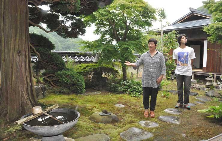 昔ながらの庭園でゲストハウスへの思いを語る上松さん(左)と上林さん