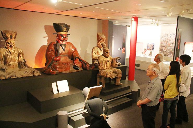 閻魔大王坐像(中央)に赤い照明を当て、人形(手前)で地獄の裁きを表現した展示=立山博物館