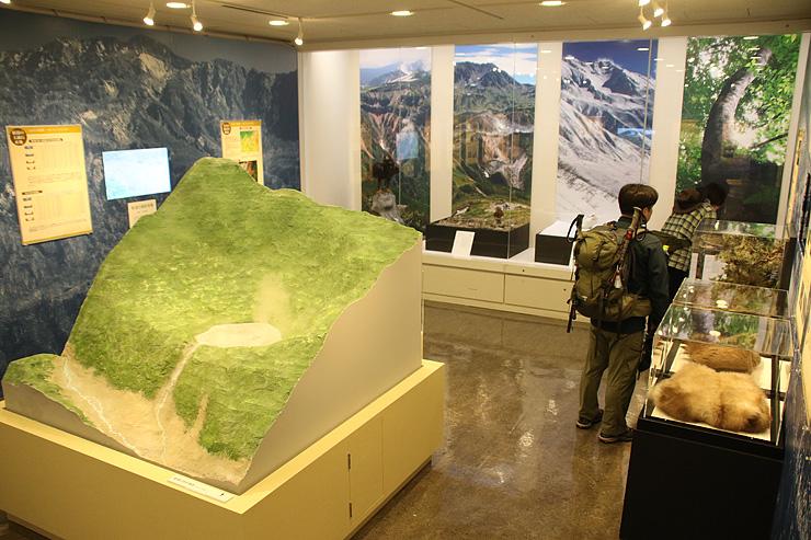 新湯の模型(手前左)や毛皮(同右)などを展示し、立山一帯の文化財を紹介している会場=立山カルデラ砂防博物館