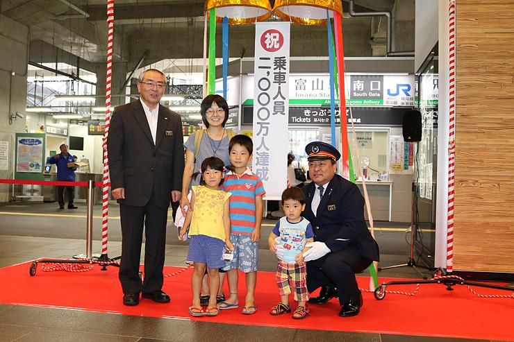 2千万人目の乗客となった渡辺さん親子(中央)ら=富山駅