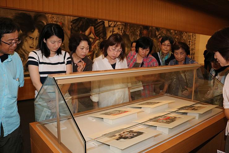 「日本神話」の色紙シリーズを見詰める来場者。後方の大作が「新富座妖怪引幕」 =県水墨美術館