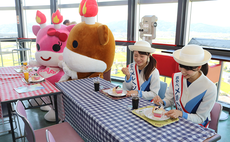 スイーツを食べる(左から)メルモモちゃん、メルギューくん、橋本さん、田中さん=クロスランドタワー
