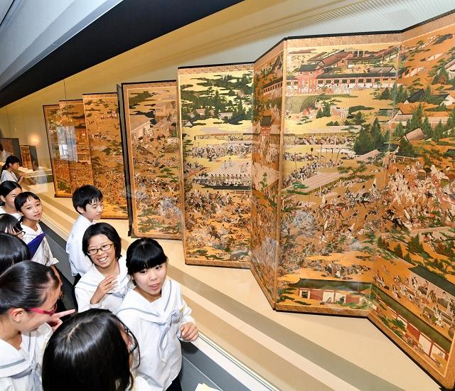 熱狂的な祭りの光景を描いた岩佐又兵衛の作品に見入る生徒ら=22日、福井市の県立美術館
