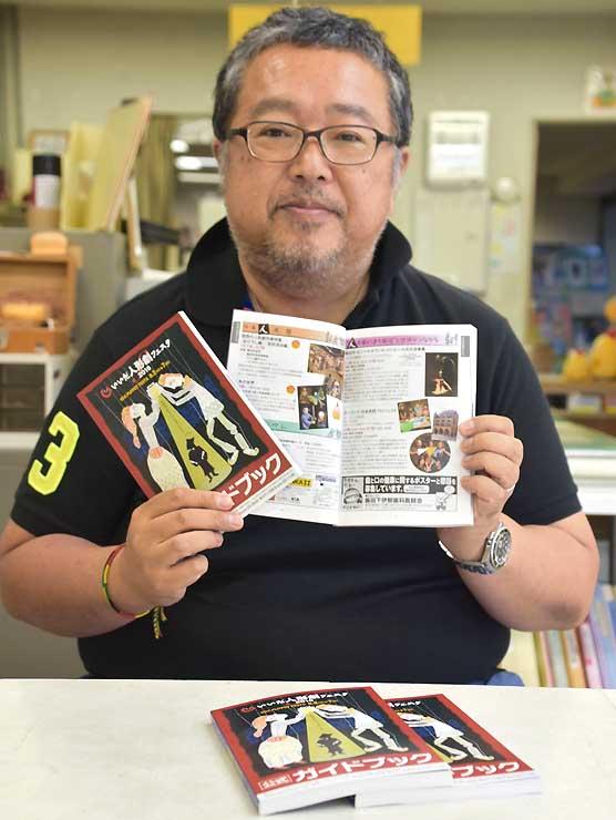 発行された公式ガイドブックを手にする原田実行委員長