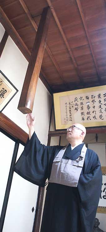 天井から下がった「幽霊柱」の横に立つ上野住職
