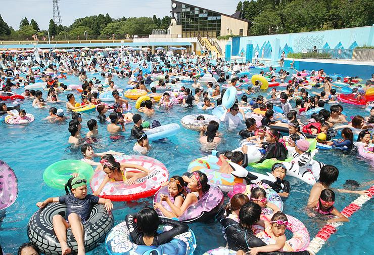 浮き輪をつかんで人工の波に揺られる大勢の家族連れや若者たち=県民公園太閤山ランド