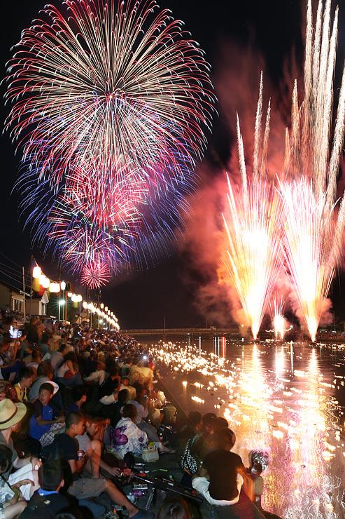 夜空を華やかに彩った大輪の花火と川面を照らす「火流し」の炎=富山市水橋の白岩川河口付近