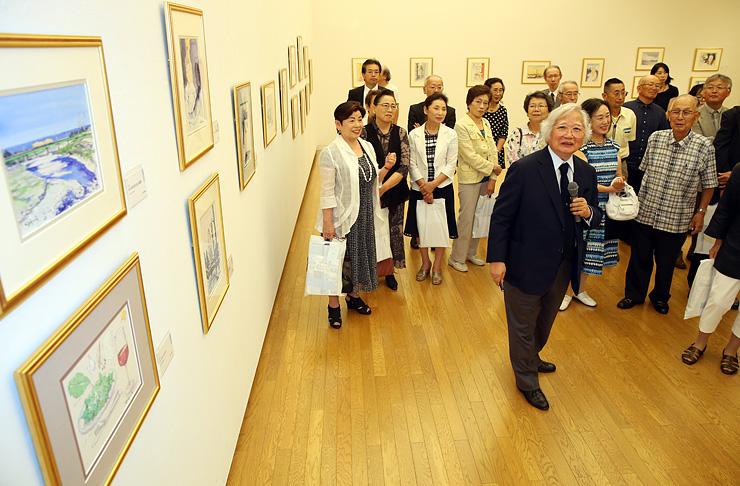 来館者に挿絵の解説をする藤森さん(中央)=砺波市美術館