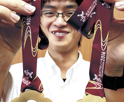 第2回金沢マラソンの完走者に贈られるメダルの試作品を披露する松浦さん=25日午前11時50分、金沢市役所