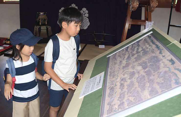 大坂夏の陣の様子を描いたびょうぶ絵の複製を見る子どもたち