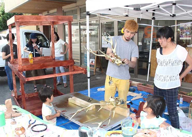 公開制作でシカの頭骨を使った飾りを作る有賀さん(右から2人目)ら。左奥が山車の本体