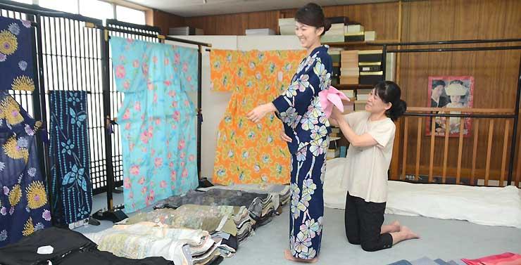 レンタルの浴衣を着付ける輿水さん(右)