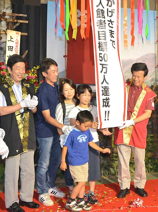 入館者50万人を達成し、くす玉を割って祝う家族連れら関係者=上田市
