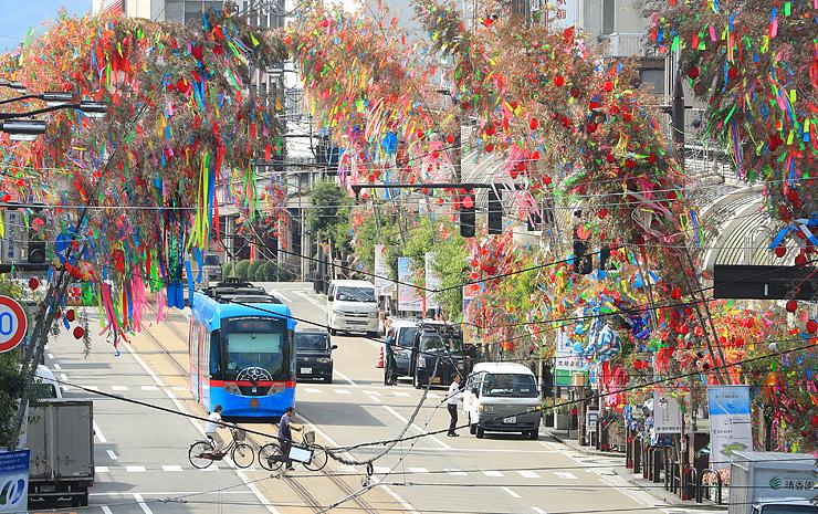 大通りに大きなアーチを描く色鮮やかな七夕飾り=高岡市末広町