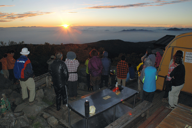 蓼科山頂ヒュッテのテラスから御来光を眺める宿泊客=7月31日午前4時50分