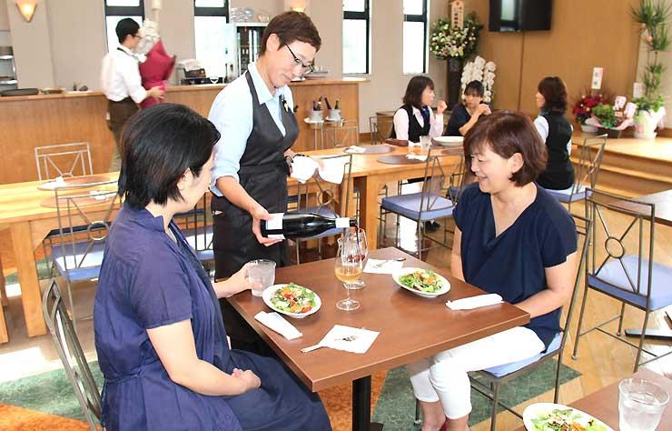 開店した東御ワインチャペルでワインを注ぐ石原浩子さん(中央)