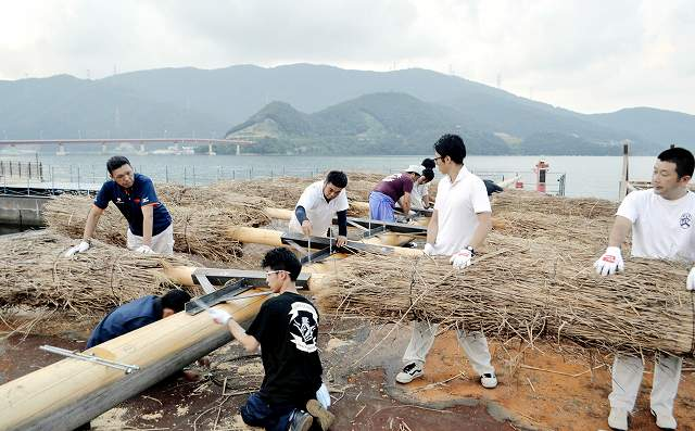 巨大たいまつの仕上げ作業に精を出すメンバーたち=2日夜、福井県おおい町