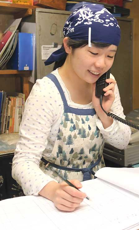宝剣山荘で電話対応する小川さん