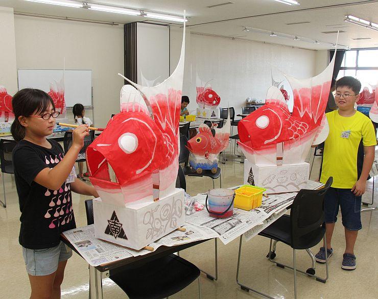 鯛車の色の塗り直し作業を行った巻南小児童=7月31日、新潟市西蒲区