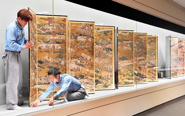 「洛中洛外図屏風(舟木本)」の展示作業に追われる関係者=5日夜、福井県立美術館