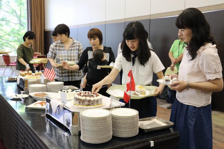 G7参加国ゆかりの菓子を皿に盛り付ける人たち
