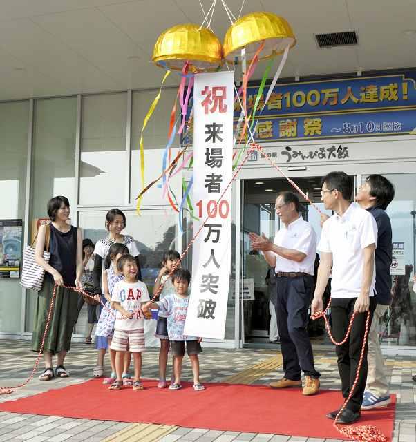 くす玉を割る高岡祥子さん(左端)の家族ら=6日、福井県おおい町成海の道の駅「うみんぴあ大飯」