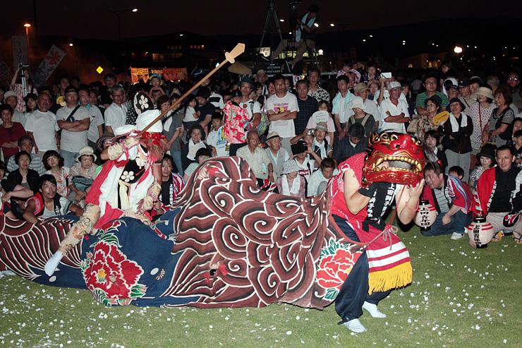 天狗が6尺棒を使う上田青年団の獅子舞を楽しむ見物客=比美乃江公園