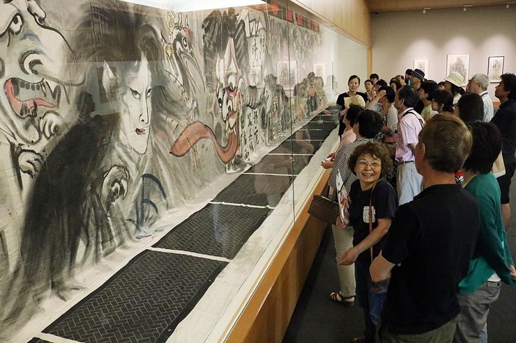 幅17メートルの巨大な引幕に見入る美術ファンたち=県水墨美術館