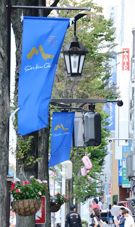 松本市の中心市街地の街灯にはOMFの旗が飾られ、開幕ムードを高めている=7日