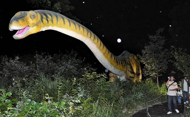 夜の森でライトアップされた恐竜のロボット=6日、福井県勝山市の長尾山総合公園