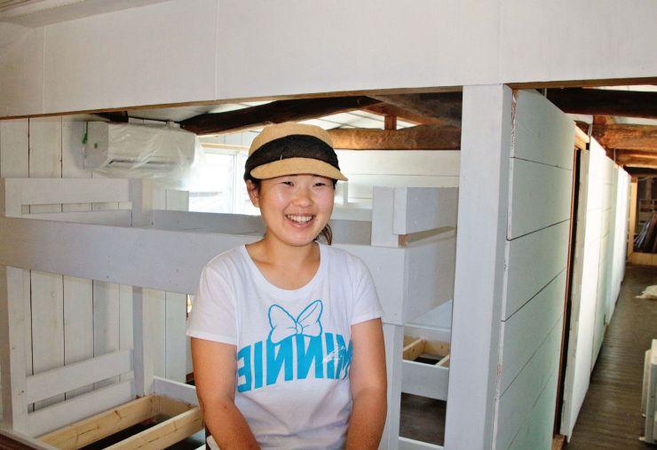 オープン間近な「おむすびのいえ」で期待を語るオーナーの青柳花子さん。2階にはずらりと2段ベッドが並ぶ=5日、粟島浦村