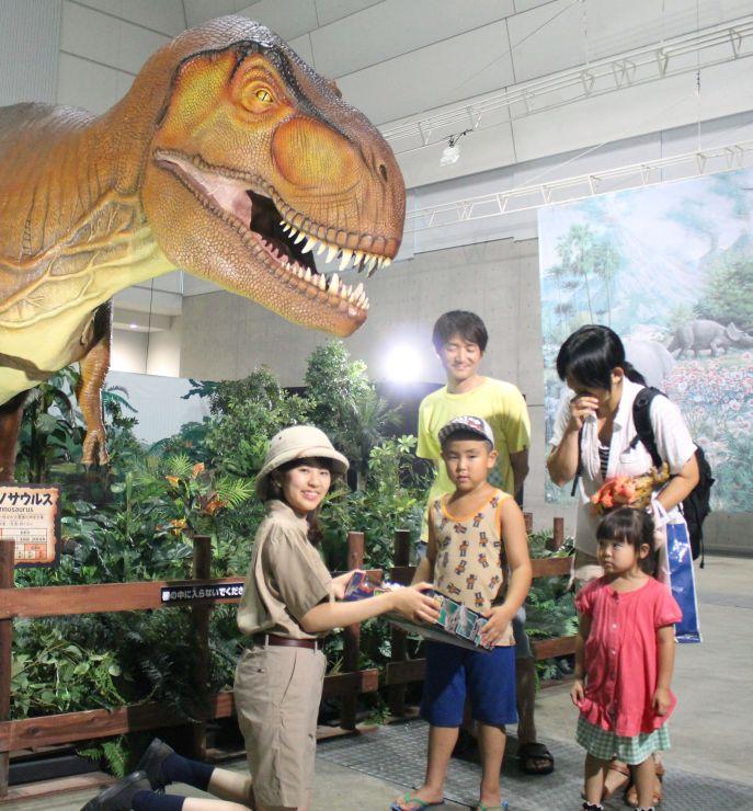 5万人目の来場者となり、記念品を受け取る男の子(左から2人目)=8日、新潟市中央区