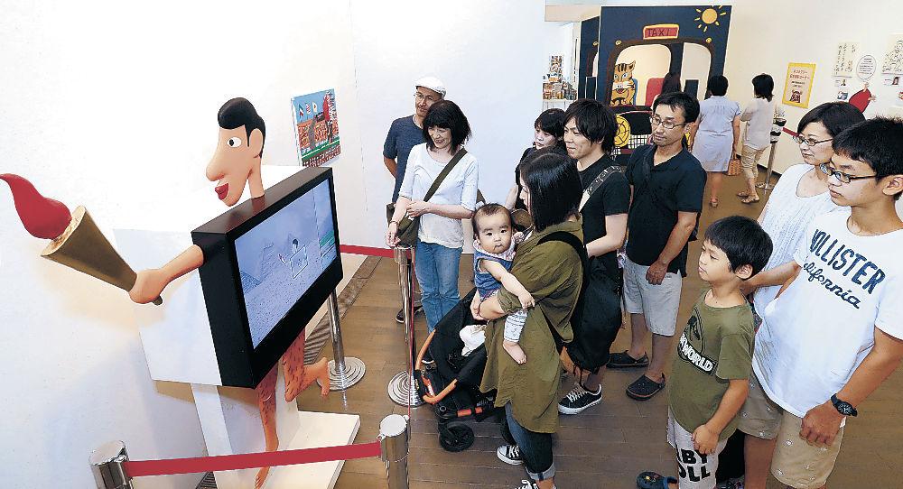 来場者数が1万人を超えたアートたけし展で、作品を鑑賞する家族連れ=金沢21世紀美術館