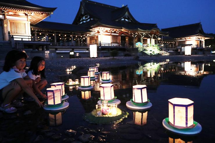 15日の万灯会を前に行われた試験点灯。境内にろうそくをともし、池に灯籠を浮かべた=鳳凰殿