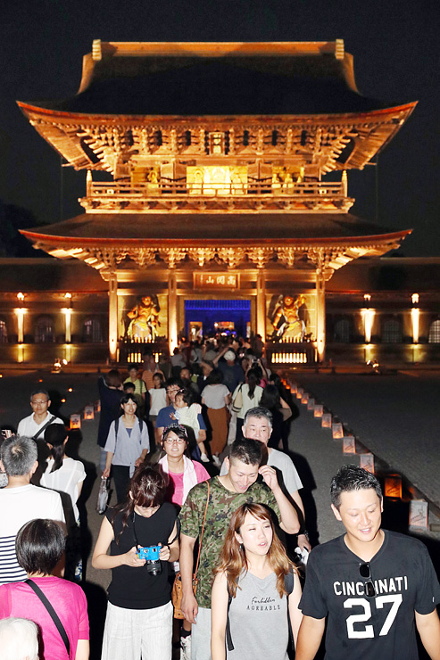 厳かに照らされた山門前の境内を歩く来場者=高岡市関本町の瑞龍寺