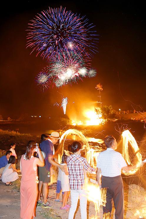 迎え火が振り回される中、夜空を彩った花火=上市町の上市川白竜橋付近(多重露光)