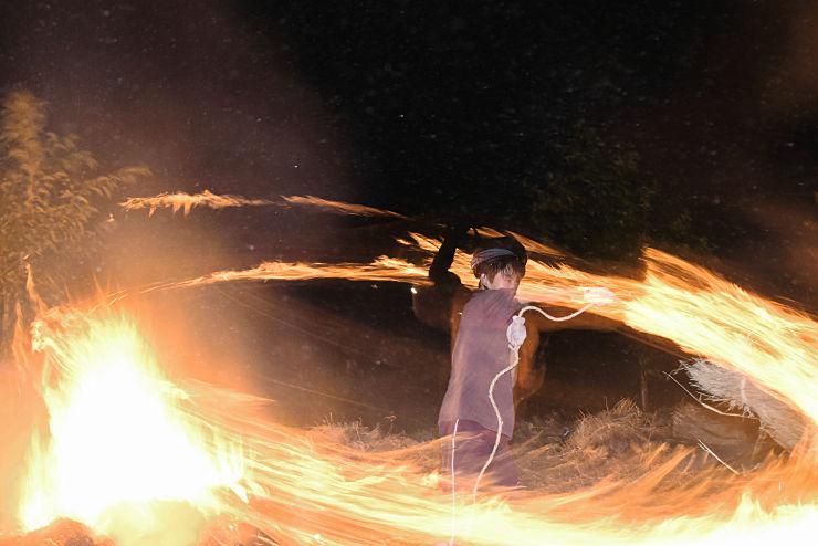 火が付いたわらの「万灯」を振り回す子ども