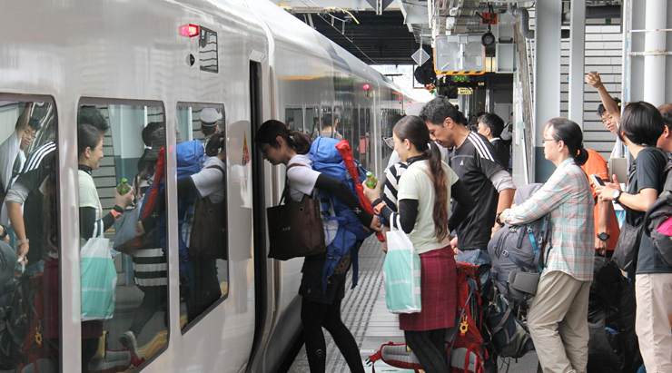 リュックサックや大きな荷物を持って特急列車に乗り込む乗客=14日午後2時20分、松本駅