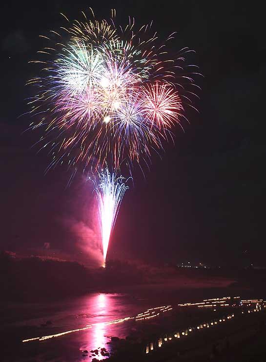 灯籠が流れる天竜川の上空を彩る打ち上げ花火=16日午後7時47分、飯田市