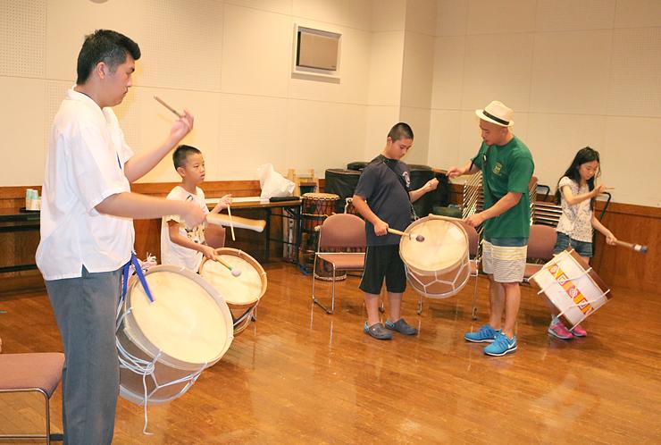 広瀬さん(左)のアドバイスを受け、太鼓を打ち鳴らす子どもら=南砺市福野文化創造センター
