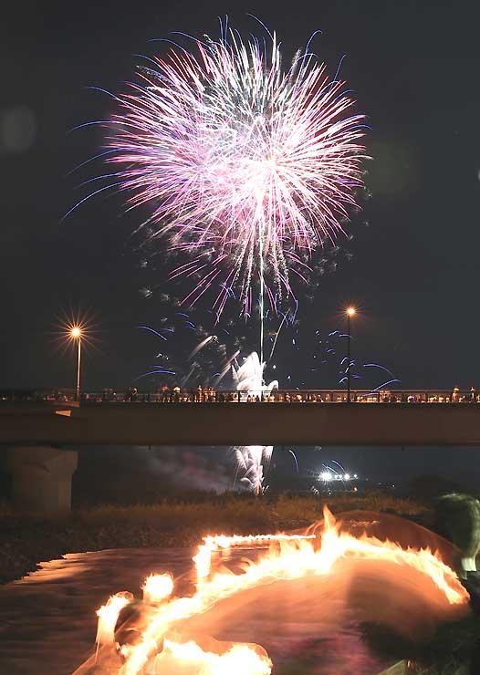 灯籠が流れ下る中、明神橋の上空を彩る打ち上げ花火=18日午後8時41分、高森町