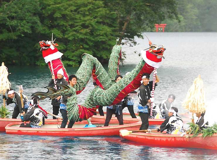 ボートに乗った志青会の若者が操る2匹の大蛇