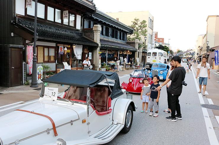 クラシックカーが並ぶ山町筋を散策する家族連れ=高岡市木舟町